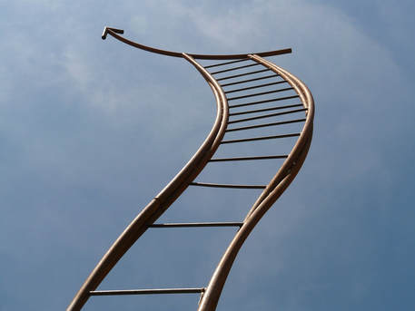 An artistic sculptured ladder with an arrow at the top pointing to the sky